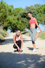 two beautiful healthy young womans running outdoor and doing fitness exercises in summer