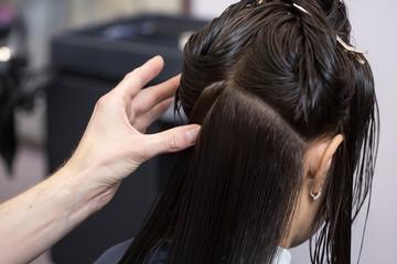 A brunette girl having her haircut. Selective focus