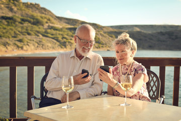 Elderly couple at the seaside using technology