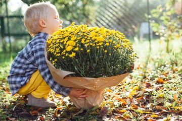 Little boy and big bouquet flowers