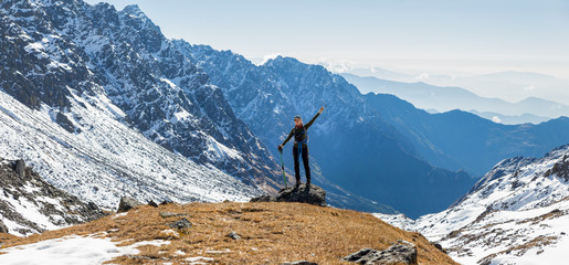 Wall Mural - Young woman tourist backpacker standing mountain edge panorama.