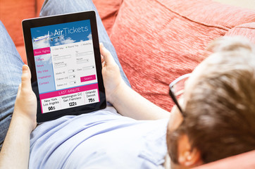 hipster on the sofa with ticket flight web at tablet