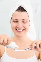 Girl applying toothpaste to toothbrush