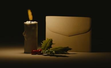 enveloppe et branche de houx éclairé par une bougie