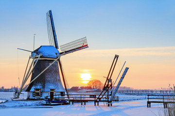 Foto op Plexiglas Molens Beautiful sunset behind an old mill in winter in the Netherlands
