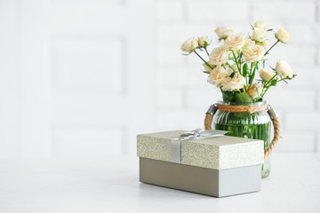 Big beautiful gift box with bouquet of flowers on the table in front of brick wall, close up