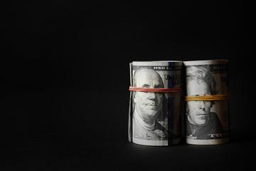 Dollars roll on black background