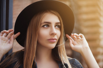 Portrait of beautiful girl wearinf hat looking up. Close up. Toned