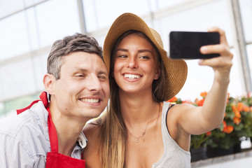 couple of flower sellers take a funny selfie in greenhouse