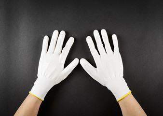 Female hands with white protective gloves on black background