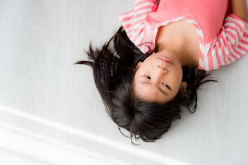 Asian girl lying on floor at home.