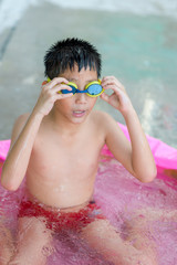 happy asian little boy playing in the pool