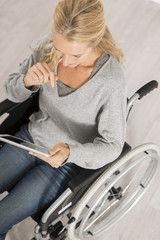 disabled woman on wheelchair using a tablet pc