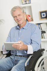 disabled man on wheelchair using tablet pc