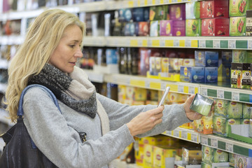 Mature woman comparing the price of tea with mobil phone