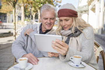 mature couple using a digital tablet at a bar terrace