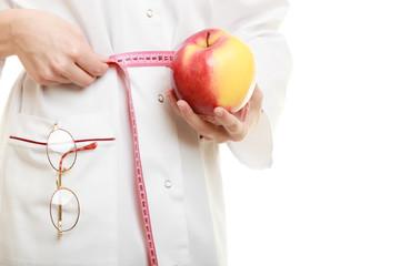 Doctor specialist holding fruit apple measuring waist