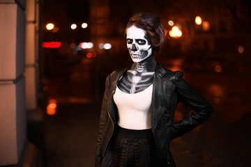 Young woman walking on city avenue. Face art for Halloween party. Street portrait