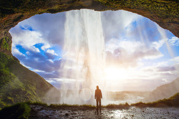 incredible waterfall in Iceland, silhouette of man enjoying amazing view of nature Wall mural