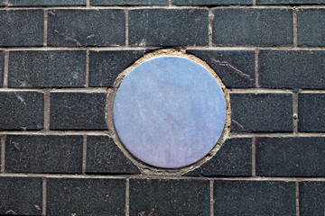 brick background with metal circle