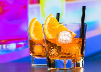Fototapete - two glasses of spritz aperitif aperol cocktail with orange slices and ice cubes on bar table, disco atmosphere background