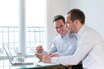 two smiling happy business men working on project in the office