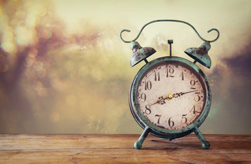 image of vintage alarm clock on wooden table in front of abstract blured background. retro filtered