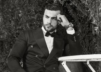 Outdoors portrait of young european fashionable man posing near garden metal table. Black-white photo.