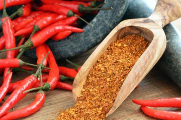 Chili - Chilipulver in Holzschaufel mit Steinmörser und Chilischoten