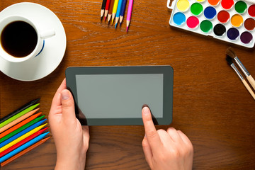 tablet and drawing tools on the table and hands