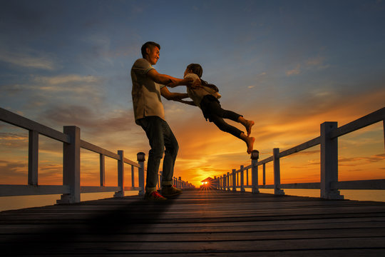 Father plays with his girl on the beach at sunset