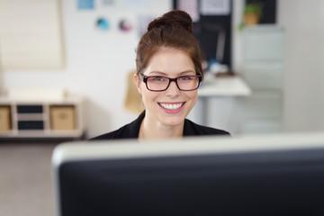 glückliche junge frau bei der arbeit am computer