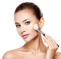 woman  applying cosmetic makeup on the face with brush