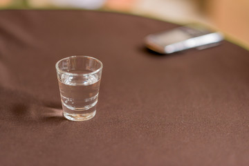 Glass of water with a mobile phone on a restaurant table