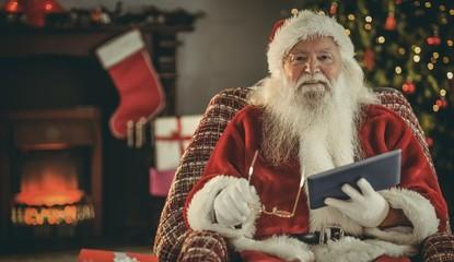 Smiling santa holding glasses and tablet