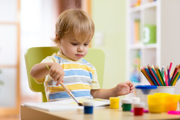 Little boy painting on creative class in kindergarten