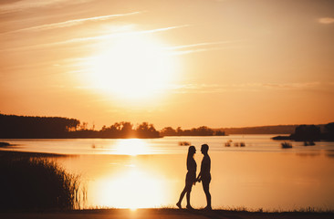 Romantic couple standing at sunset. copy space