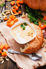 mashed pumpkin soup with herbs , cream , crackers and bread with sesame seeds on a wooden background