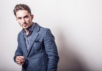 Elegant young handsome man in stylish blue jacket. Studio fashion portrait.