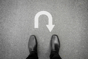 Black shoes standing in front of u turn symbol