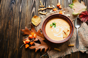 mashed pumpkin soup in a clay plate with herbs , cream , crackers and bread with sesame seeds on a wooden background