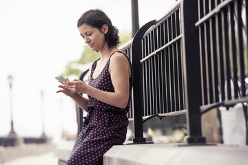 A woman pausing on a street, sitting and checking her cell phone.