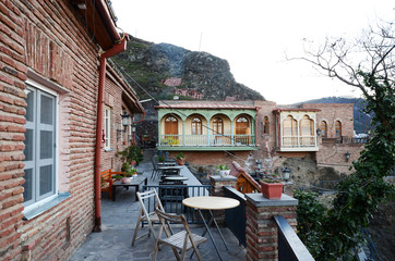 The outdoor terrace with tables. Residential houses on the hillside in Old Tbilisi