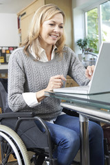 Disabled Woman In Wheelchair Using Laptop At Home