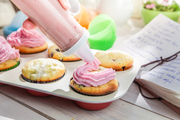 Decorating sweet cupcakes with cream