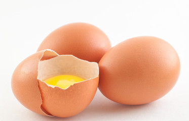 Three raw eggs with yolk on a white background
