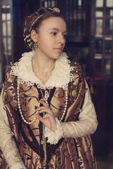 Woman wearing renaissanse gold dress reading Bible