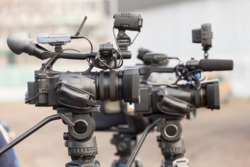 Modern digital video cameras covering an event