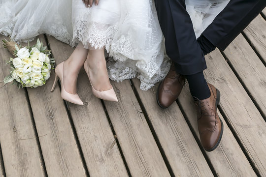 feet of bride and groom, wedding shoes (soft focus). Cross proce