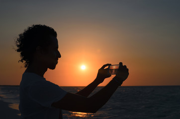 Silhouete of young man taking photo of sunset at seaside with his smartphone